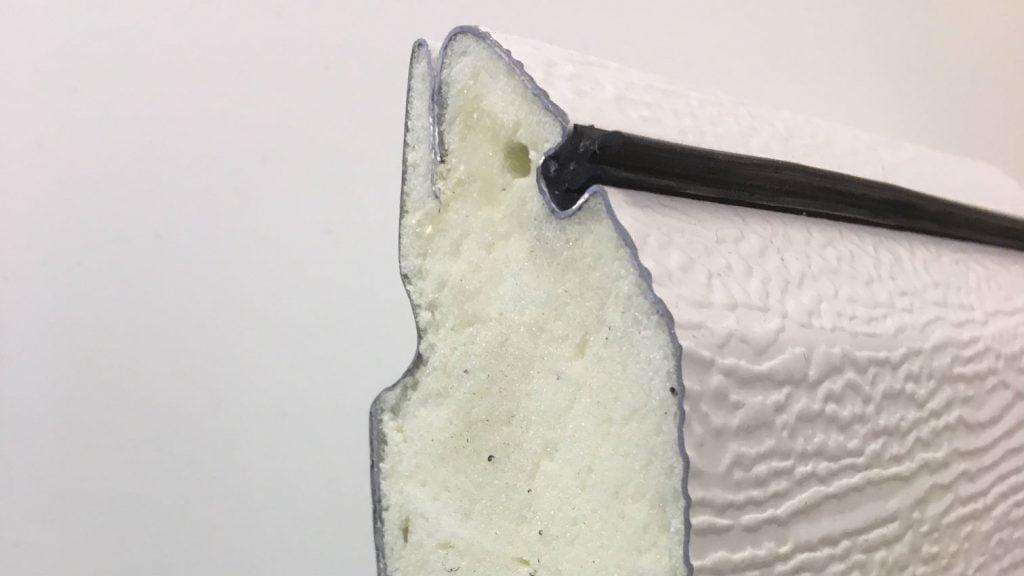 Nærbilde av et tverrsnitt av et isolert garasjeportelement. En skummet, isolerende kjerne limer sammen to stålplater og skaper god stabilitet og isolasjonsevne i porten. Lobas. Fotografi, 2019