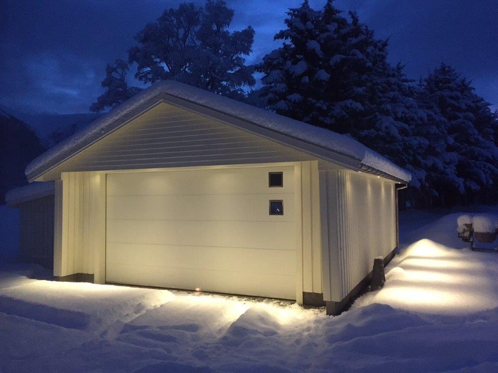 Garasje med Lobas garasjeport med vindu. Vinter, kveld og snø. Fotografi