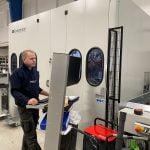 Ronny betjener (data)styringen av maskinene som bearbeider aluminiumsprofiler inne på Lobas garasjeporters fabrikk. Fotografi 2019.