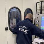 Ronny ser inn i «operasjonsrommet», der maskineriet jobber med aluminiumsprofiler på anlegget til Lobas garasjeporter. Fotografi 2019.