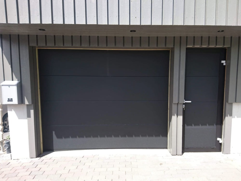 Antrasittgrå garasjedør og garasjeport fra Lobas i samme utførelse på lysegrått trebygg. Fotografi 2020.